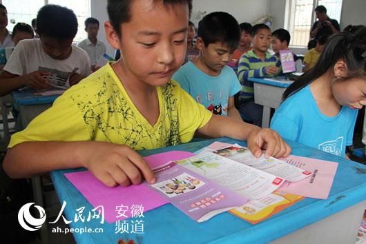 小学生认真阅读宣传材料
