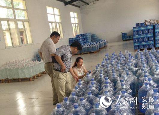 执法人员查看桶装饮用水产品标签