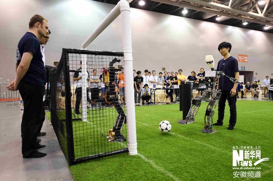 on AD队的机器人球员(右)在类人组成人型半决赛中射门.最终,