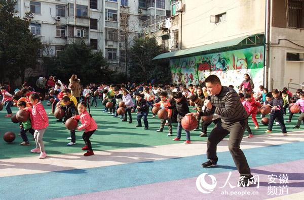 人民网讯 为了激发幼儿对篮球的兴趣,促进动作协调发展,提高幼儿的身体素质,近日,合肥市长江路幼儿园开展了全园幼儿参与的篮球户外运动。 据了解,此次活动是作为幼儿园的体育特色游戏长期持续的开展。每周三全园幼儿分成大、中、小三个年级进行分批练习,幼儿园还特地请来了专业的篮球教练龙老师向小朋友传授新本领。  经过上一学期的训练,小朋友的拍球技能和动作更加娴熟专业,不仅能够快速地按照教练的口令做出动作,而且单手拍球、双手拍球、两手交替拍球、转身拍球、行进拍球等也都像模像样。小朋友们积极认真的态度和熟练的动作,都