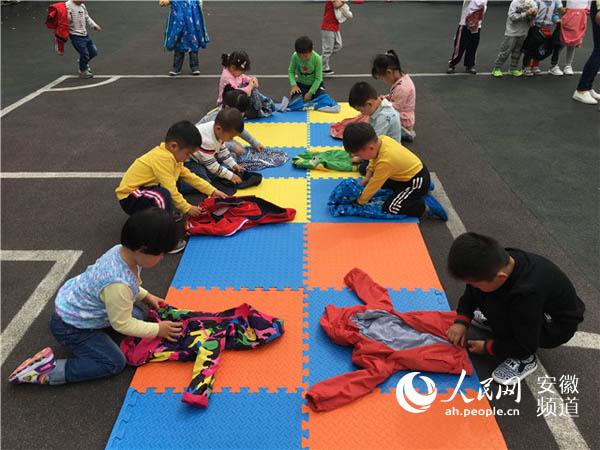 人民网讯 为让幼儿学会叠衣服的简单生活技能,提高幼儿自我服务意识, 4月21日,合肥市荣城幼儿园组织小班年级组的孩子们,在幼儿园操场开展了叠衣服比赛的快乐大放送活动。通过比赛鼓励幼儿尝试自己叠衣服,提高幼儿的动手能力和生活自理能力。  老师在活动开始前将每个班分成了三组,每组10位小朋友。每一轮小一班、小二班、小三班各派一组幼儿参赛,共进行三轮小组预赛。哨子一声响,小朋友们立即冲上战场叠衣服,别看小班幼儿年龄小,却个个身手不凡,动作麻利。关关门,抱一抱,点点头,弯弯腰,孩子们边念儿歌边叠衣服。
