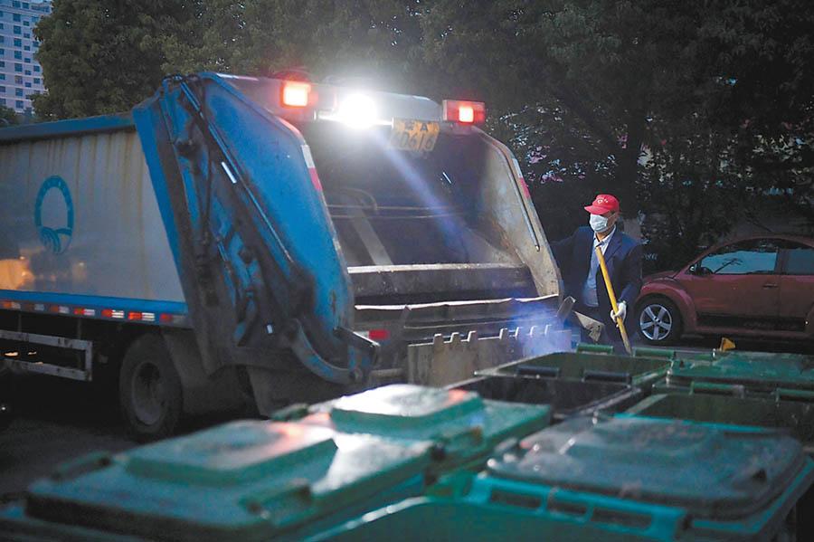 4月25日23时15分,位于合肥市北一环一小区内,环卫工人将白天产生的垃圾装进小型垃圾清运车。 吴文兵 李迎昕 摄