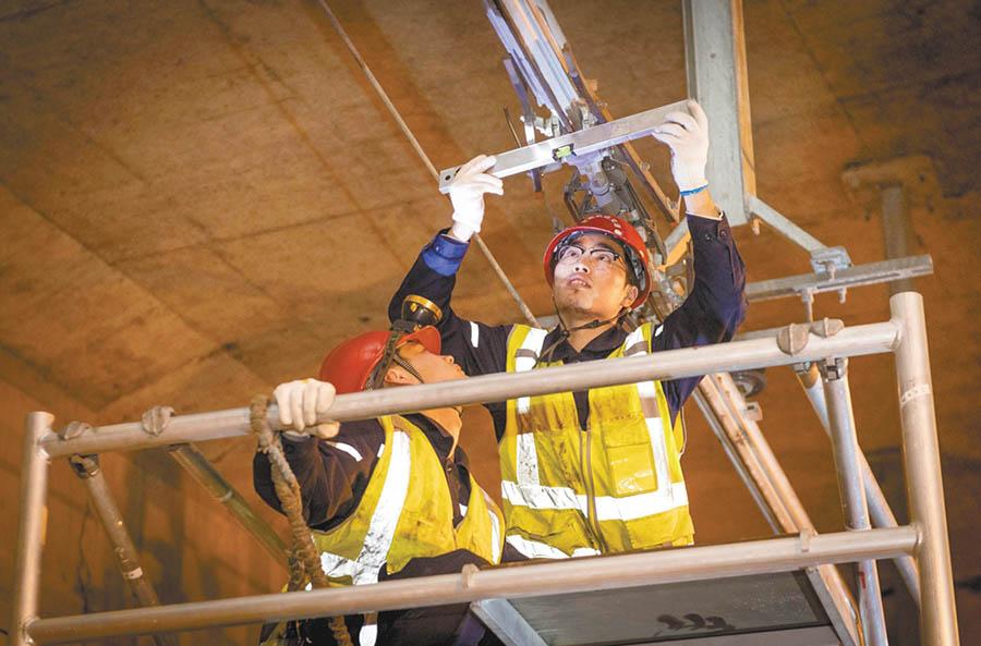 4月25日2时21分,在合肥轨道交通一号线合肥火车站站隧道中,地铁接触网检修工在测量电网水平值。 李博 摄