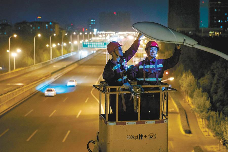 4月28日22时13分,在合肥市徽州大道高架合肥南站方向上桥口,工作人员正在维修一处出现故障的路灯。范柏文 摄