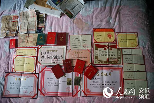 里面赫然是厚厚一叠奖状证书,老人轻轻地把这些整齐摆放在床上.图片