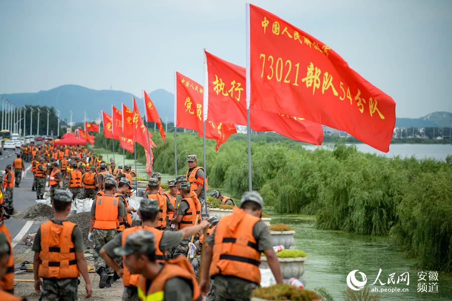 部队官兵装填沙袋,加高加固环巢湖大道长临河段。苗子健摄