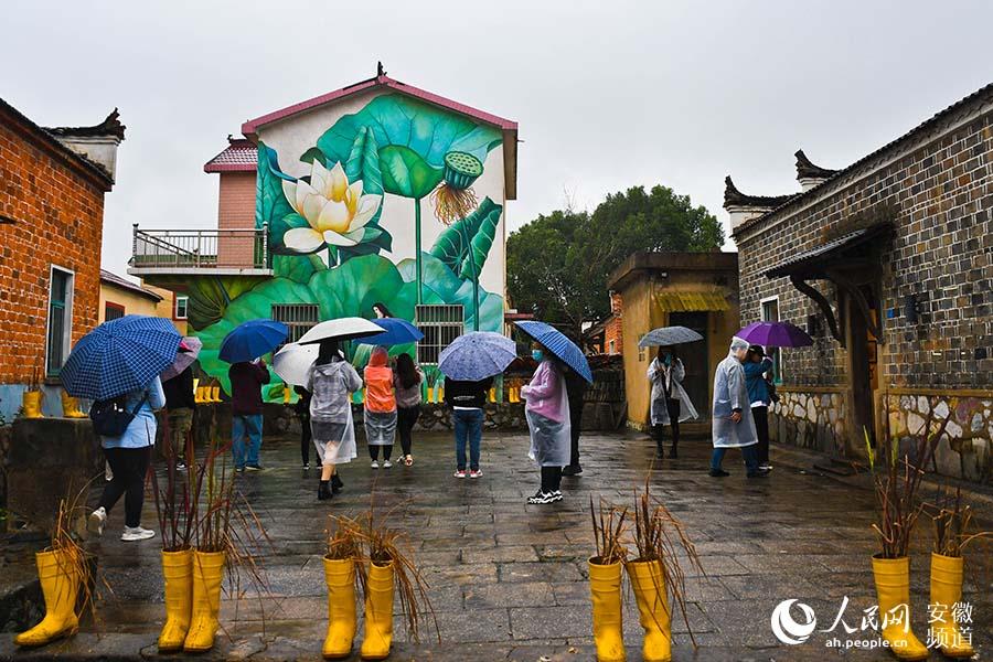 众多游客参观犁桥村的特色壁画。周坤摄